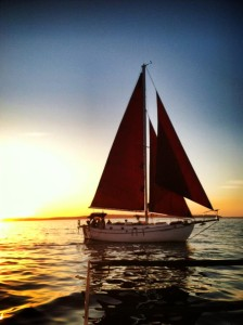Satori shrouded by the sunset. Photo by Tom Muir of Seattle Sailing Club